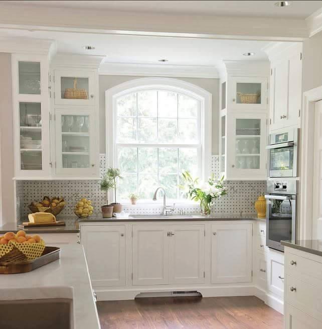 Cucina su misura bianca come cornice alla finestra.